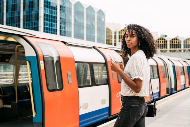 Donna di colore che per mezzo del telefono cellulare a londra sotterranea