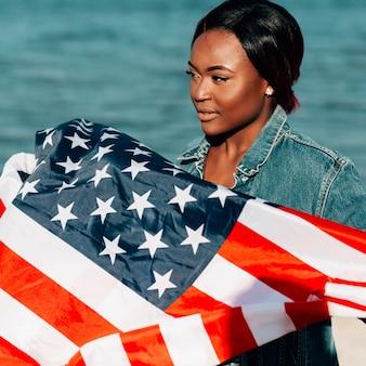 Donna di colore che sta e che tiene bandiera americana