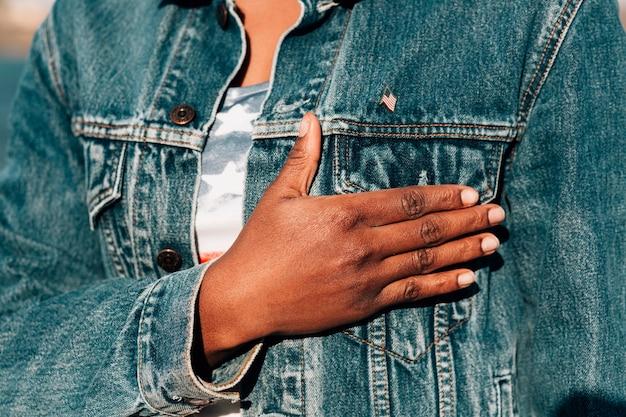 Donna di colore che tiene la mano sul cuore