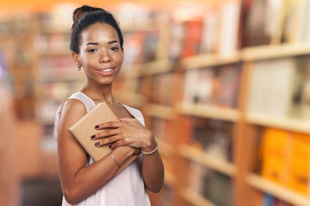 Donna di colore che tiene una pila di libri