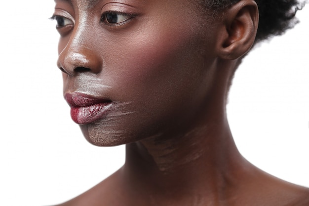 Donna di colore con il mezzo fronte su trucco, concetto di bellezza