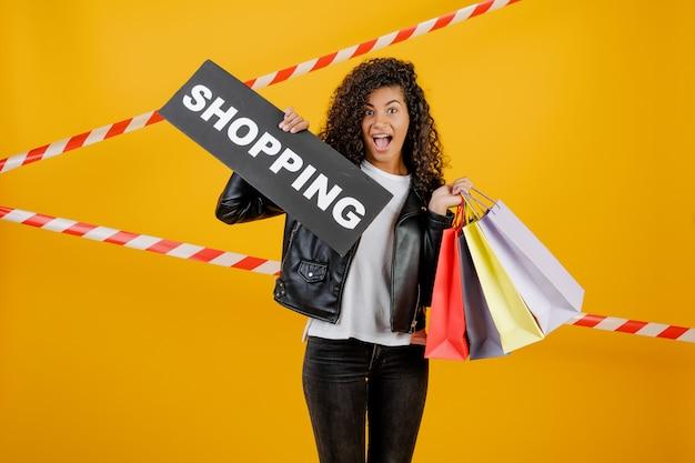 Donna di colore con il segno di acquisto e sacchetti della spesa variopinti isolati sopra giallo con nastro adesivo