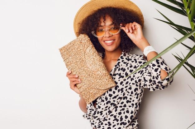 Donna di colore con l'acconciatura africana in cappello di paglia che posa sopra la parete bianca. ritratto in studio flash.