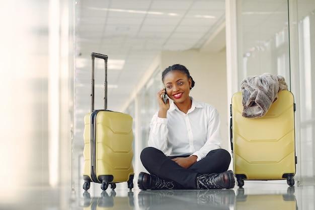 Donna di colore con la valigia in aeroporto
