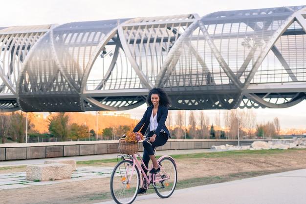 Donna di colore di affari che guida una bicicletta d'annata nella città