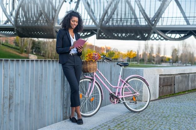 Donna di colore di affari con la bicicletta d'annata dal fiume che esamina il suo ordine del giorno