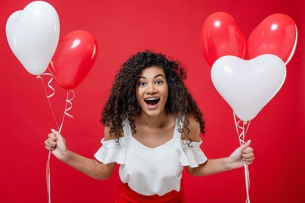 Donna di colore di grido emozionante che giudica i palloni bianchi e rossi variopinti isolati su rosso