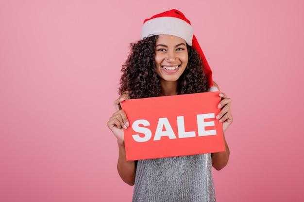 Donna di colore emozionante che tiene il segno rosso di vendita del copyspace e che porta il cappello di santa isolato sopra il rosa