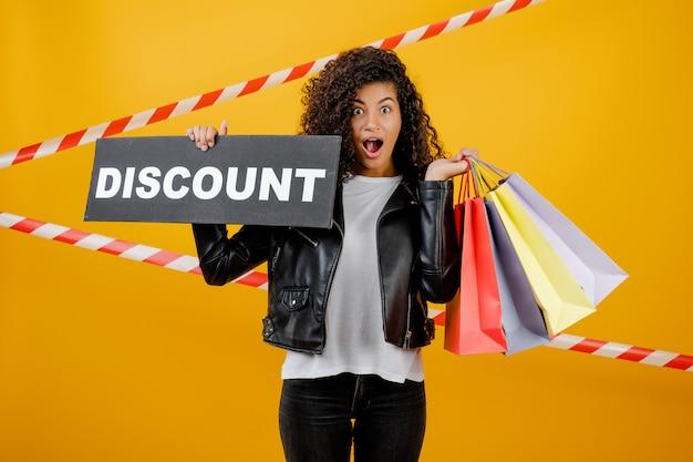 Donna di colore emozionante con il segno di sconto e sacchetti della spesa variopinti isolati sopra giallo con nastro adesivo