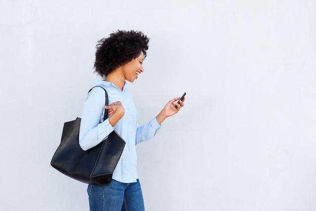 Donna di colore felice che cammina con il telefono cellulare e la borsa su fondo grigio