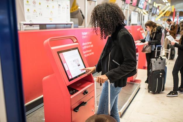 Donna di colore felice che usando la macchina di registrazione all'aeroporto che ottiene la carta d'imbarco.