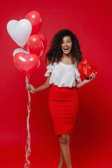 Donna di colore felice con il contenitore di regalo a forma di cuore e gli aerostati variopinti isolati sulla parete rossa