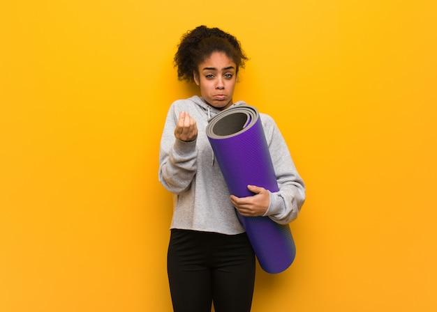 Donna di colore giovane fitness facendo un gesto del bisogno. tenendo un tappetino.