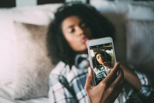 Donna di colore graziosa che fa un selfie sul sorridere del letto