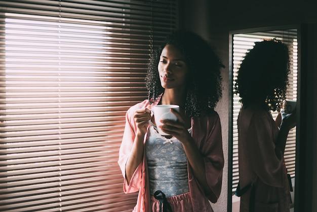 Donna di colore graziosa che sta alla finestra con la tazza di caffè