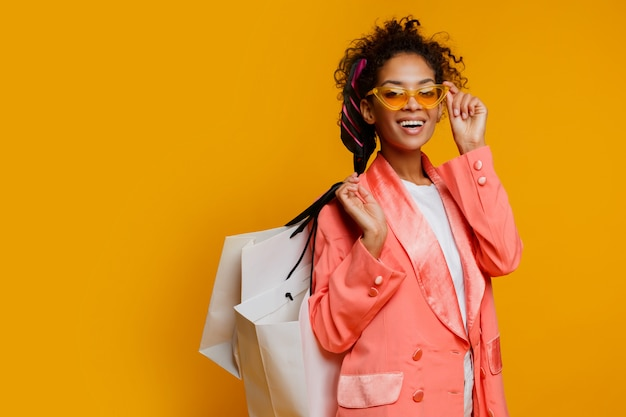 Donna di colore graziosa con il sacchetto della spesa bianco che controlla fondo giallo. look alla moda primaverile alla moda.