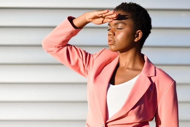 Donna di colore, modello di moda, in piedi sul muro urbano