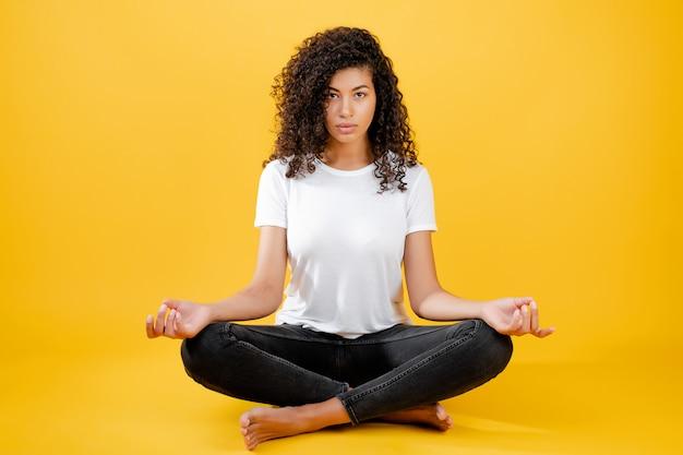 Donna di colore rilassata che medita nella posa di yoga isolata sopra giallo