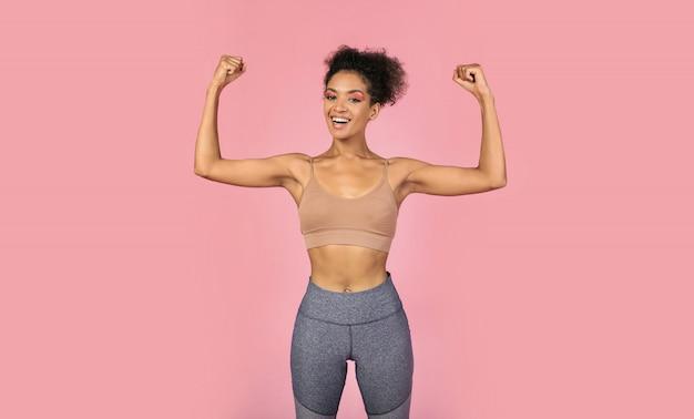 Donna di colore sicura che mostra muscolare e potenza. femmina africana in sportwear stiloso in posa su sfondo rosa.