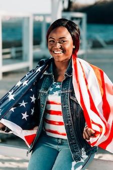 Donna di colore sorridente avvolta nella bandiera americana