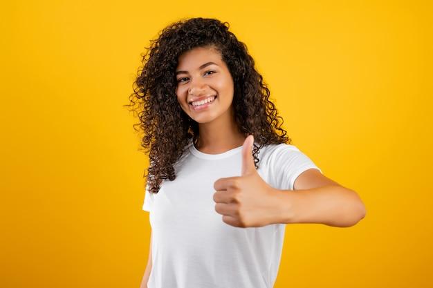 Donna di colore sorridente felice che mostra i pollici in su isolati sopra giallo