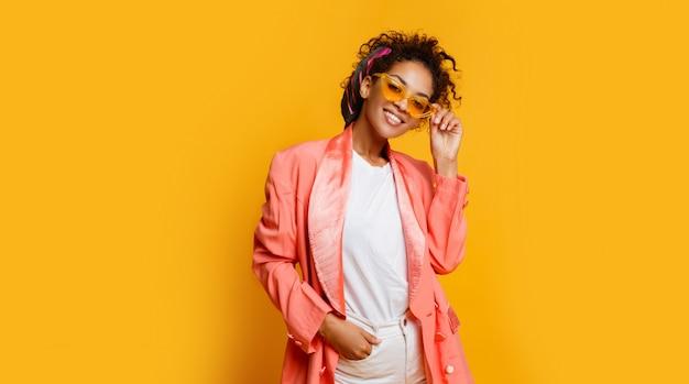 Donna di colore sorridente sicura nella posa rosa alla moda del rivestimento dell'interno su fondo giallo.