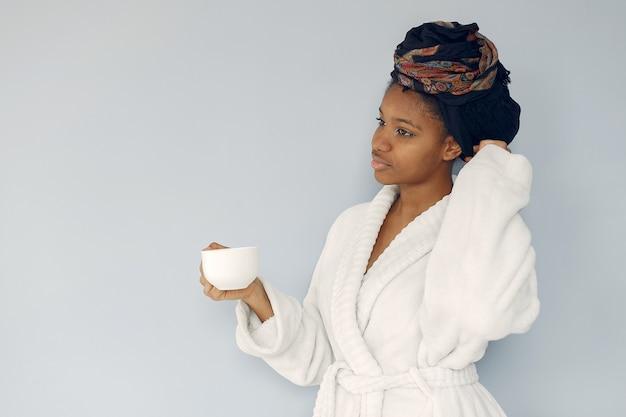 Donna di colore sveglia che sta su una parete bianca