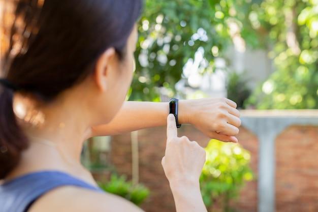 Donna di concetto di sanità che controlla il monitor del braccialetto di forma fisica sull'orologio astuto