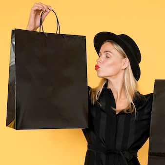 Donna di concetto di vendita venerdì nero che bacia gesto di borsa della spesa