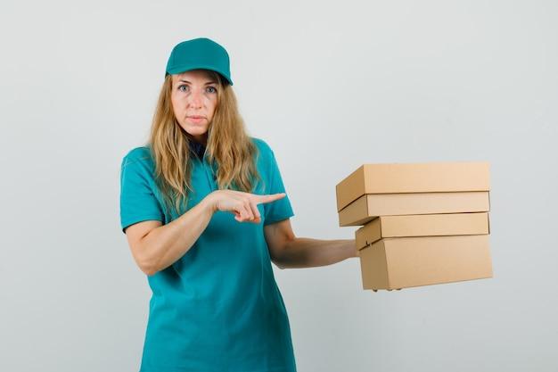 Donna di consegna che indica a scatole di cartone in t-shirt, berretto