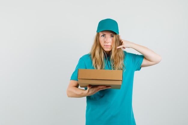 Donna di consegna che tiene la scatola di cartone con il gesto del telefono in t-shirt, cappuccio