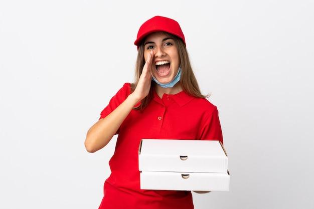 Donna di consegna della pizza che tiene una pizza e che protegge dal coronavirus con una maschera sopra la parete bianca isolata che grida con la bocca spalancata