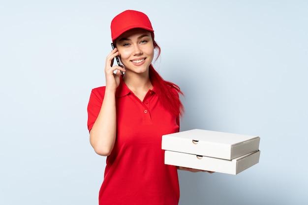 Donna di consegna della pizza che tiene una pizza sopra il muro isolato mantenendo una conversazione con il telefono cellulare con qualcuno