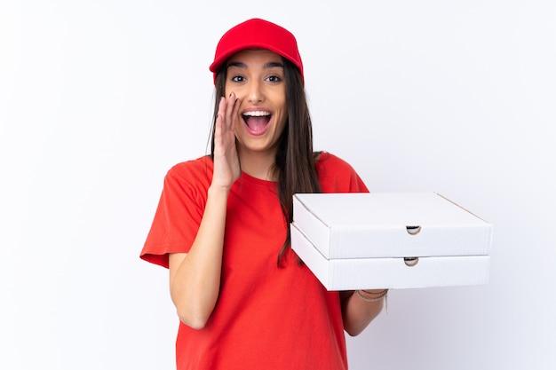 Donna di consegna della pizza che tiene una pizza sopra la parete bianca che grida con la bocca spalancata
