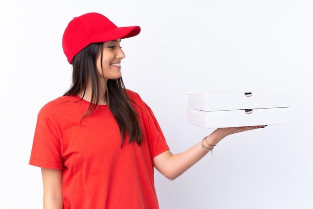 Donna di consegna della pizza che tiene una pizza sopra la parete bianca con l'espressione felice
