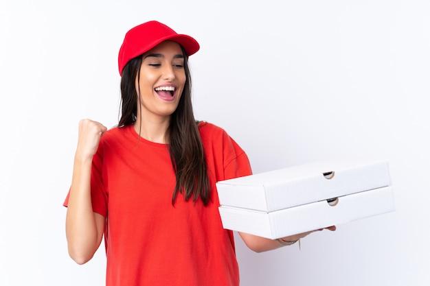 Donna di consegna della pizza che tiene una pizza sopra la parete bianca isolata che celebra una vittoria