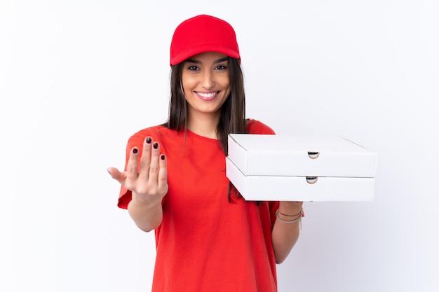 Donna di consegna della pizza che tiene una pizza sopra la parete bianca isolata che invita a venire con la mano. felice che tu sia venuto