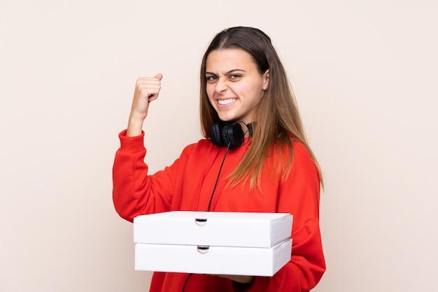 Donna di consegna della pizza che tiene una pizza sopra la parete isolata che celebra una vittoria