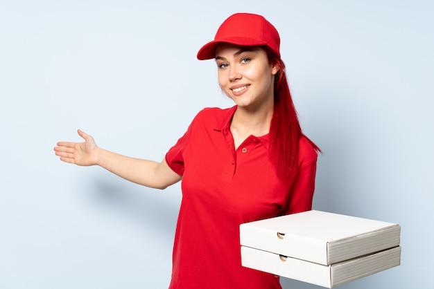 Donna di consegna della pizza che tiene una pizza sopra la parete isolata che estende le mani al lato per invitare a venire