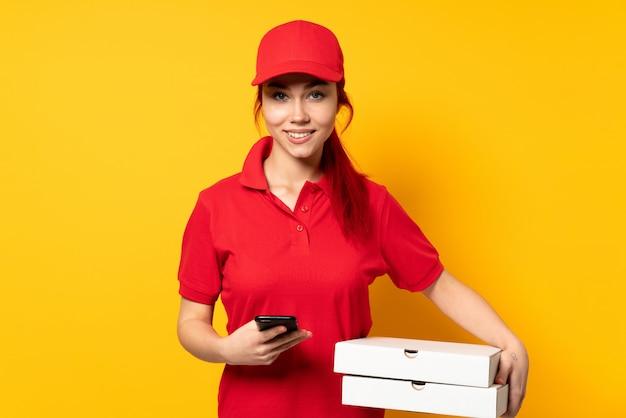 Donna di consegna della pizza che tiene una pizza sopra la parete isolata che invia un messaggio con il cellulare