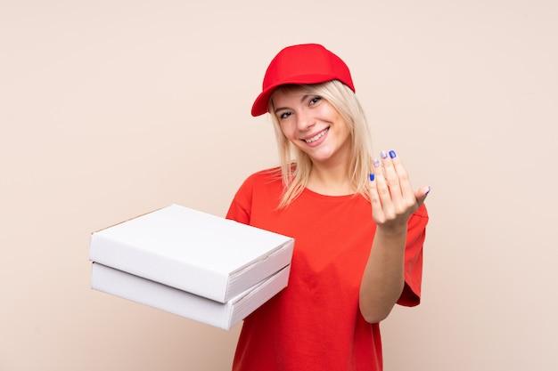 Donna di consegna della pizza che tiene una pizza sopra la parete isolata che invita a venire con la mano. felice che tu sia venuto