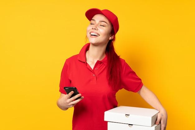Donna di consegna della pizza che tiene una pizza sopra la parete isolata con il telefono nella posizione di vittoria