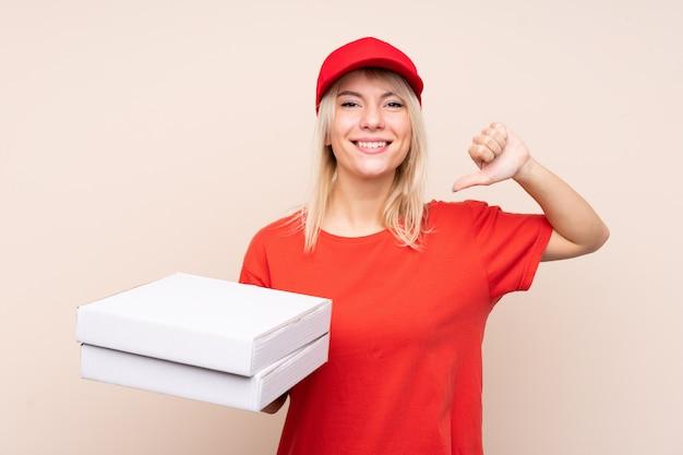 Donna di consegna della pizza che tiene una pizza sopra la parete isolata fiera e soddisfatta di sé