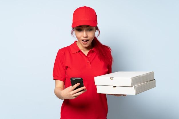 Donna di consegna della pizza che tiene una pizza sopra la parete isolata sorpresa e che invia un messaggio