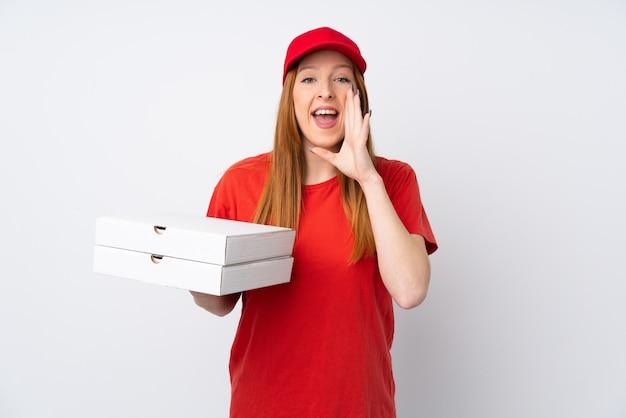 Donna di consegna della pizza che tiene una pizza sopra la parete rosa isolata che grida con la bocca spalancata