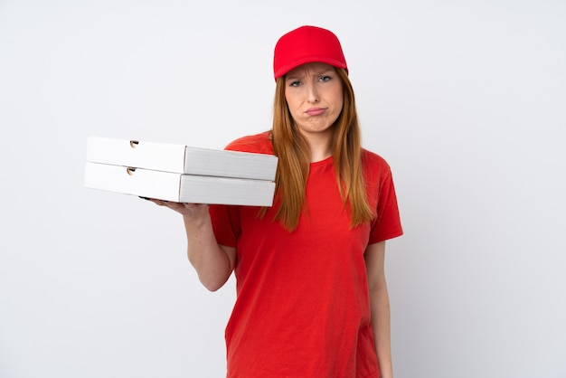 Donna di consegna della pizza che tiene una pizza sopra la parete rosa isolata con l'espressione triste