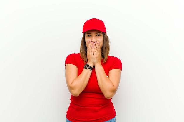 Donna di consegna felice ed eccitata, sorpresa e stupita che copre la bocca con le mani, ridacchiando con un'espressione carina contro il bianco