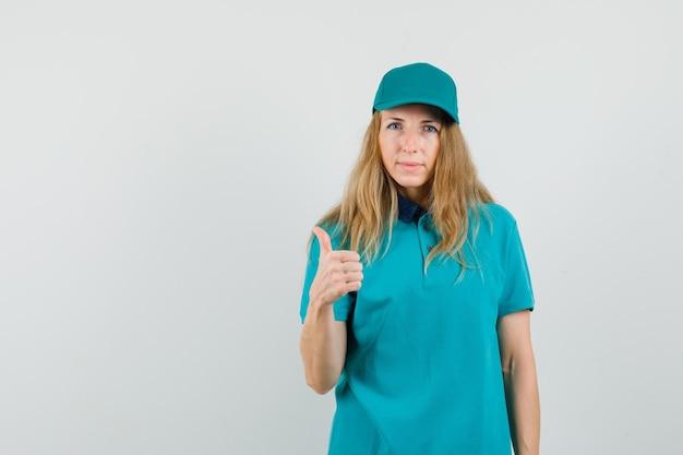 Donna di consegna in t-shirt, cappuccio che mostra il pollice in su e sembra sicura