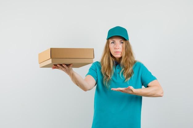 Donna di consegna in t-shirt, cappuccio che mostra una scatola di cartone