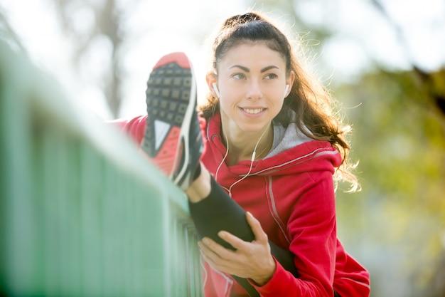 Donna di corridore felice facendo esercizi di stretching sul ponte